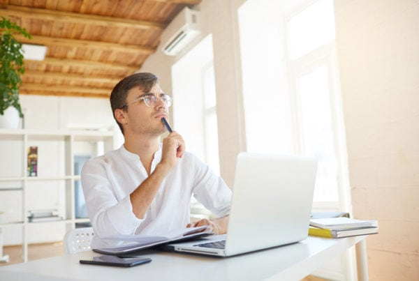 Indoor shot of thoughtful concentrated young businessman wears white shirt