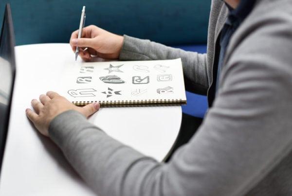 Hand holding notebook with drew brand logo creative design